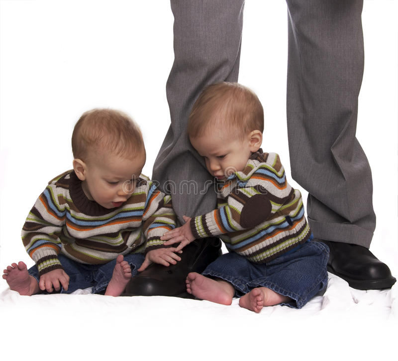 拿着相同的行程孪生的男婴爸爸 免版税图库摄影