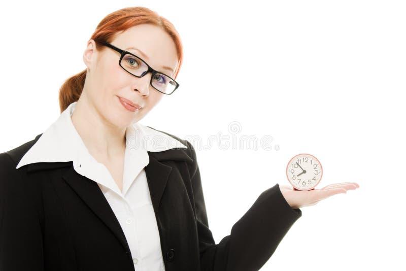 拿着相当微笑的妇女的时钟 免版税图库摄影