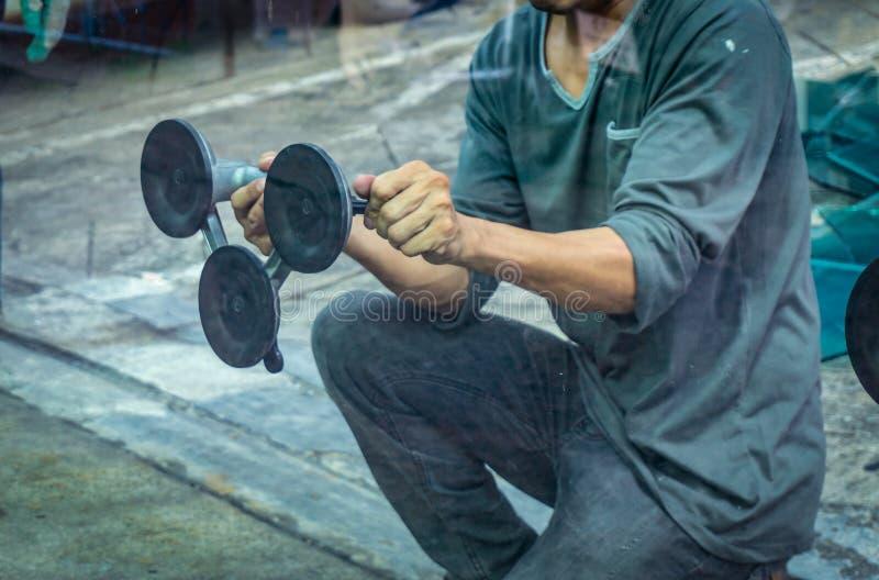 拿着真空吸杯子工具的工作者的手 选择聚焦 免版税库存照片