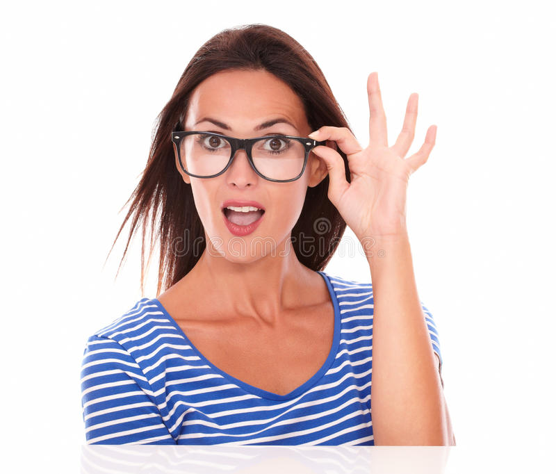 拿着眼镜的愉快的女性,当微笑时 免版税库存图片