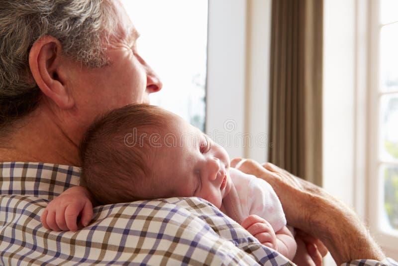 拿着睡觉的新出生的小孙女的祖父 免版税图库摄影