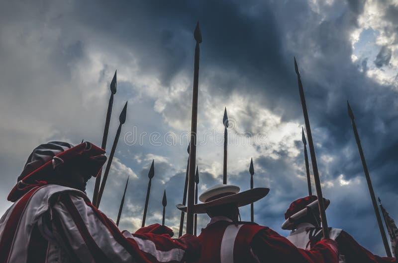 拿着矛的中世纪骑士战士准备好争斗 红色和白色制服 拍摄与剧烈的天空在风暴前 免版税库存图片