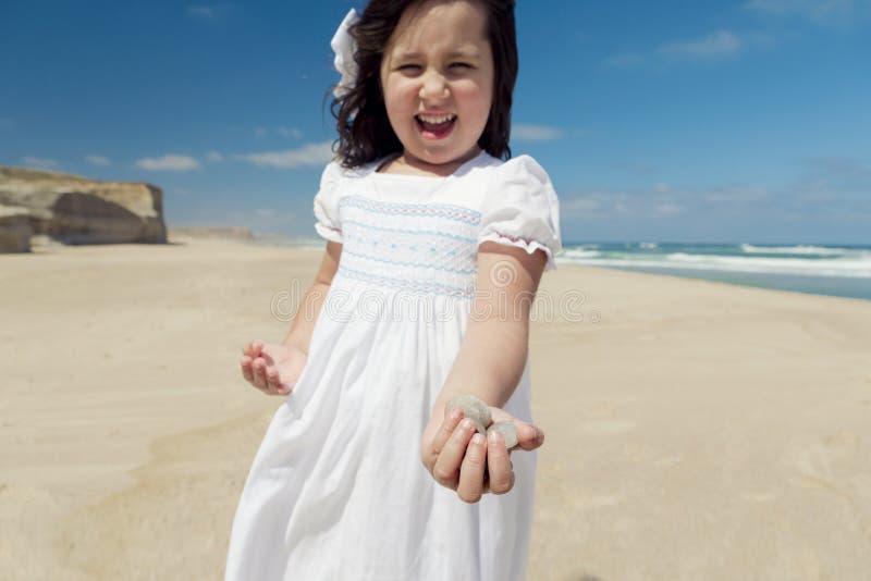 拿着石头的海滩的女孩 库存图片