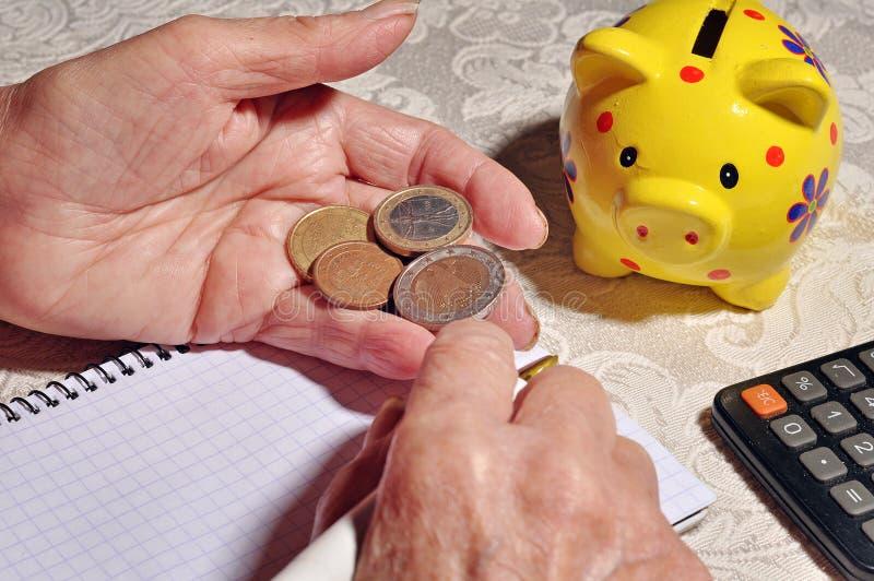 拿着硬币的一个老妇人的手 图库摄影