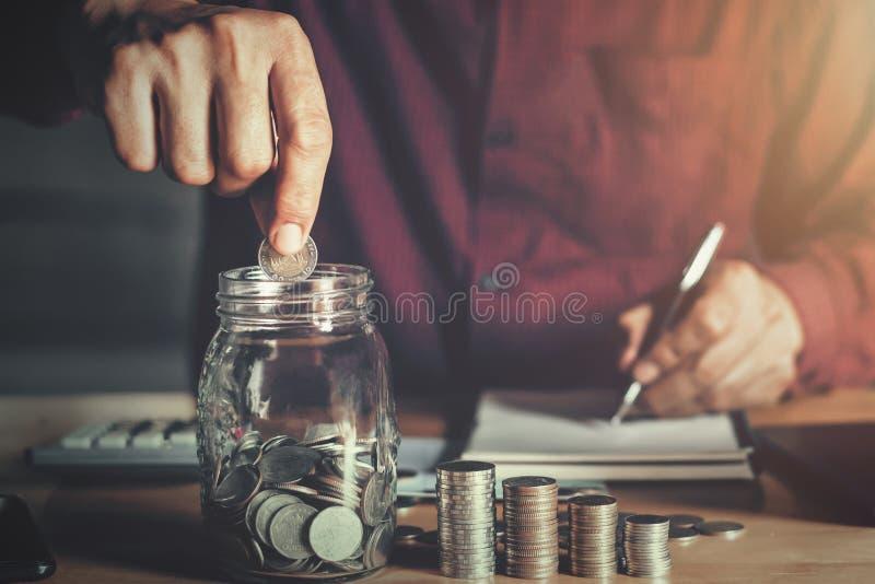 拿着硬币的商人投入在玻璃 概念攒钱和财务 图库摄影