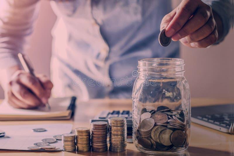 拿着硬币的商人投入在玻璃 概念攒钱和财务 免版税库存图片