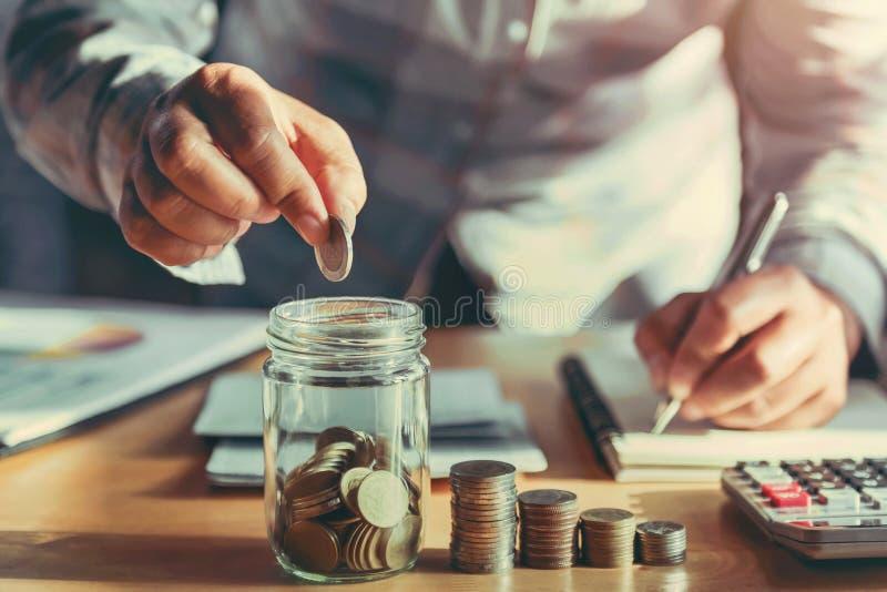 拿着硬币的女实业家投入在玻璃 概念攒钱和财务会计 免版税库存照片