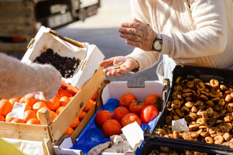 拿着硬币的消费者做购买在果子 免版税库存照片
