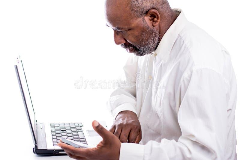 拿着硬盘和看计算机膝上型计算机的非裔美国人的男性技术员 免版税库存照片