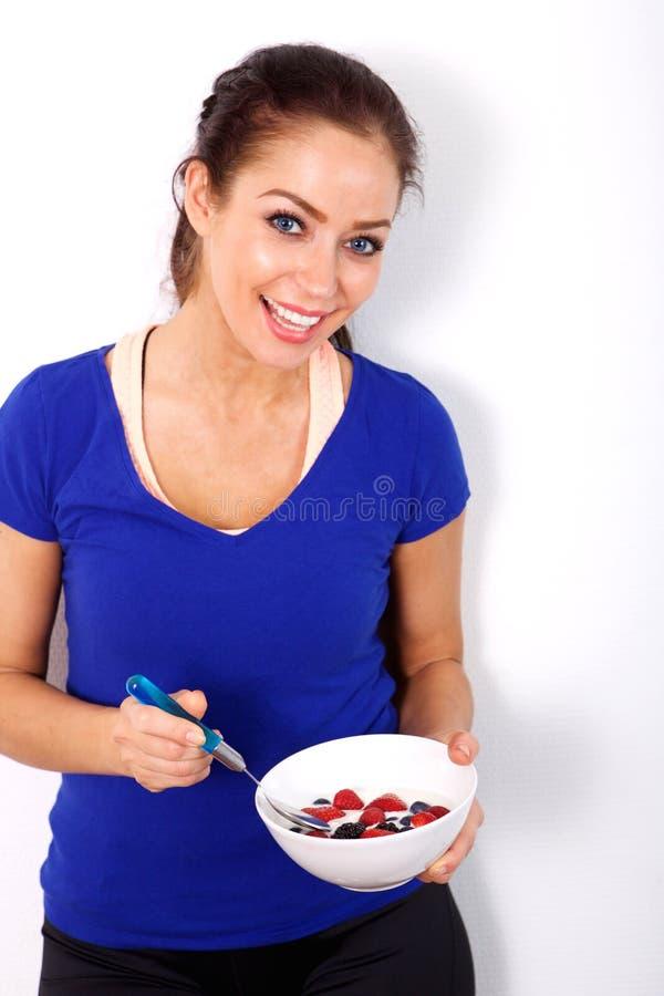 拿着碗健康食物的微笑的妇女反对白色背景 库存照片