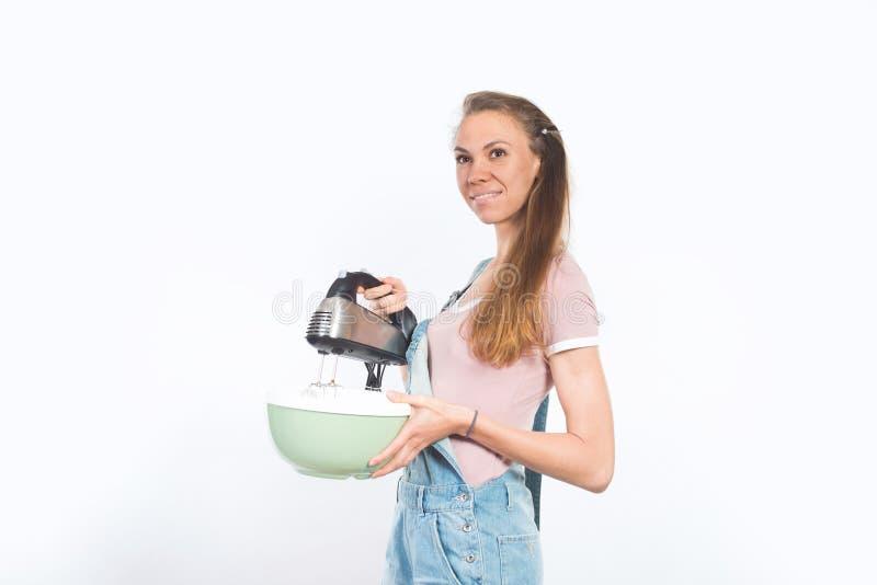 拿着碗和搅拌器的年轻可爱的微笑的妇女 库存照片