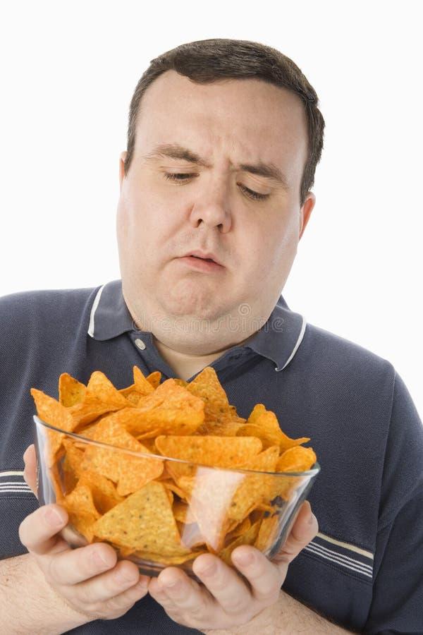 拿着碗烤干酪辣味玉米片的迷茫的肥胖人 免版税库存照片