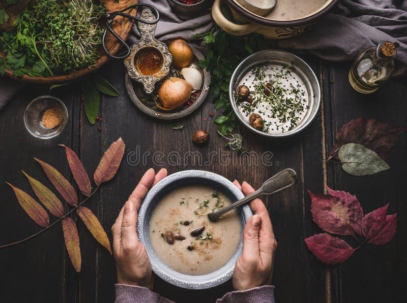 拿着碗用在黑暗的土气厨房用桌背景的秋天菜栗子乳脂状的汤的女性手与秋天离开, t 免版税库存照片