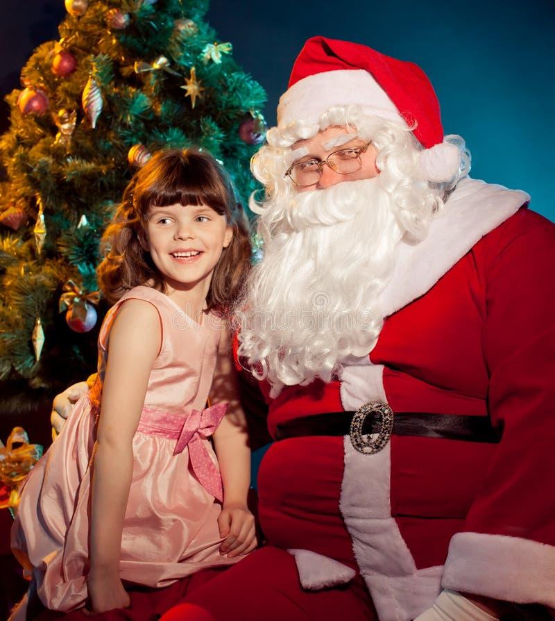 拿着礼品的圣诞老人和小女孩 免版税库存图片