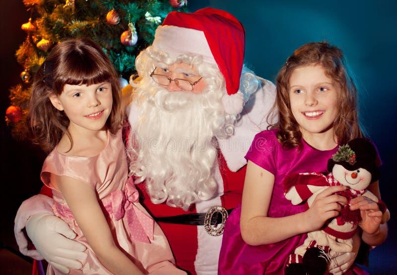 拿着礼品的圣诞老人和小女孩 免版税库存照片