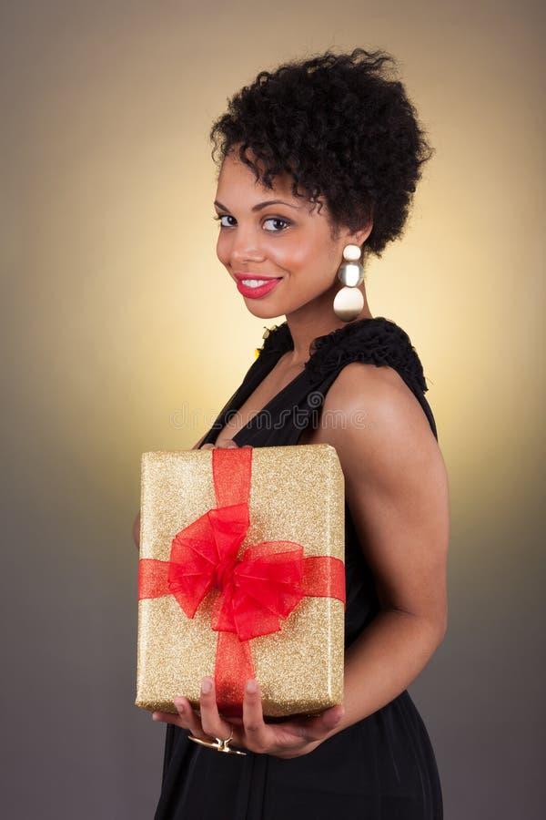拿着礼品的新非洲裔美国人的妇女 库存照片