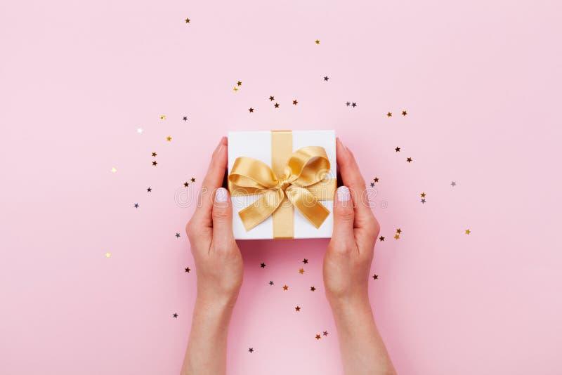 拿着礼物或当前箱子的妇女手装饰了在桃红色淡色台式视图的五彩纸屑 平的位置构成为生日 免版税库存照片