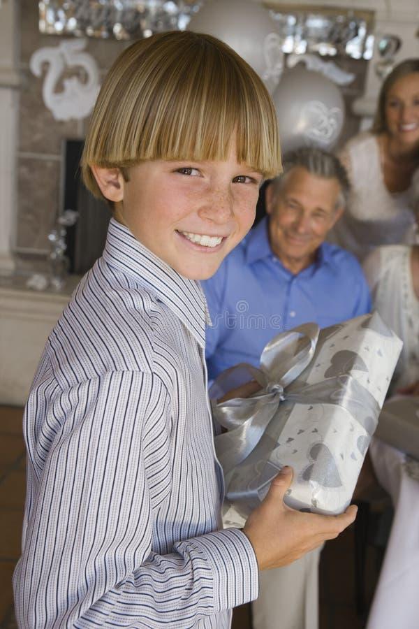 拿着礼物的十几岁的男孩 库存图片