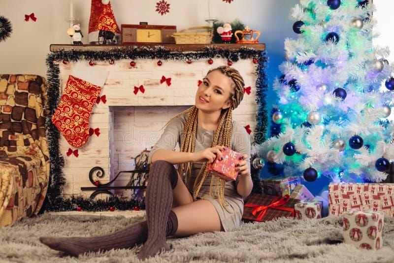 拿着礼物的可爱的少妇和在圣诞树附近坐 免版税库存图片