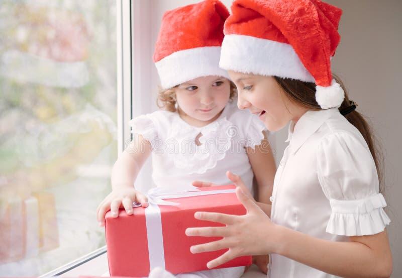拿着礼物的圣诞老人帽子的两个小女孩 图库摄影