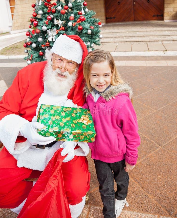 拿着礼物的女孩和圣诞老人 免版税库存照片