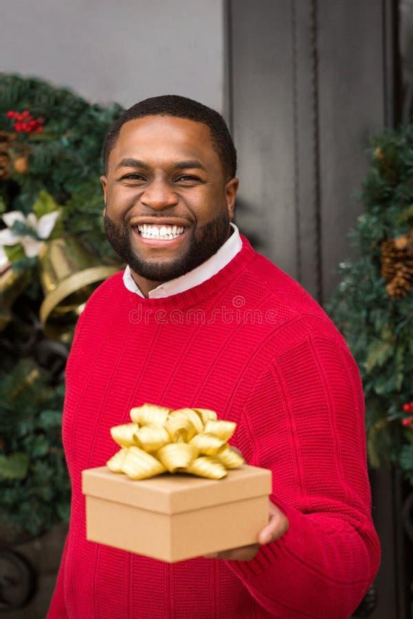 拿着礼物的年轻非裔美国人的人 库存图片