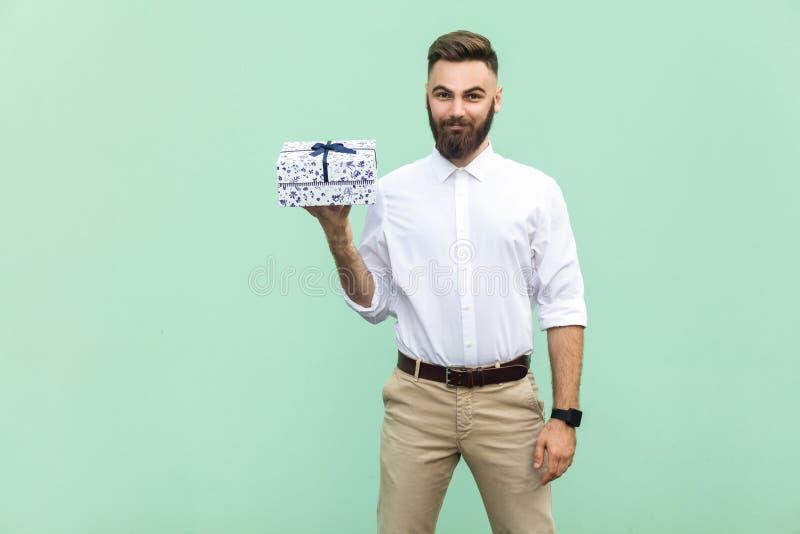 拿着礼物盒和看照相机和暴牙的微笑的年轻成人商人 免版税图库摄影
