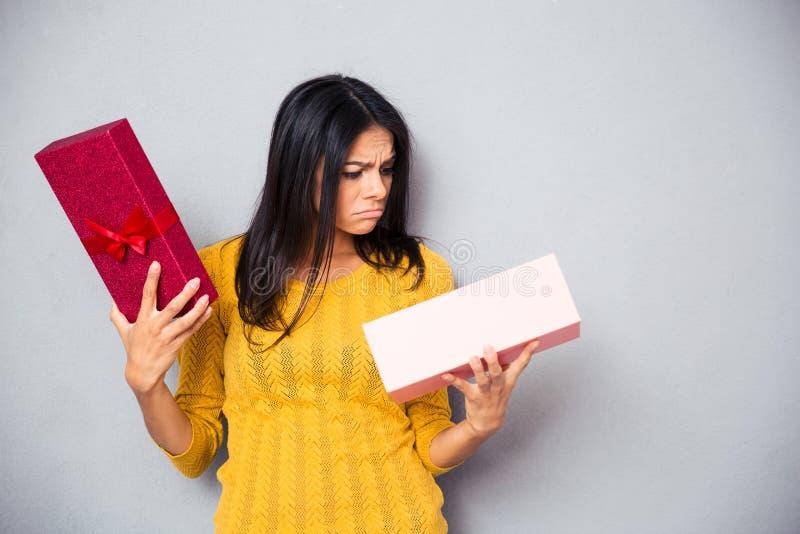 拿着礼物盒的不快乐的少妇 库存图片