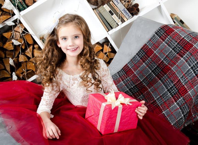 拿着礼物盒的公主礼服的可爱的微笑的小女孩 免版税库存图片