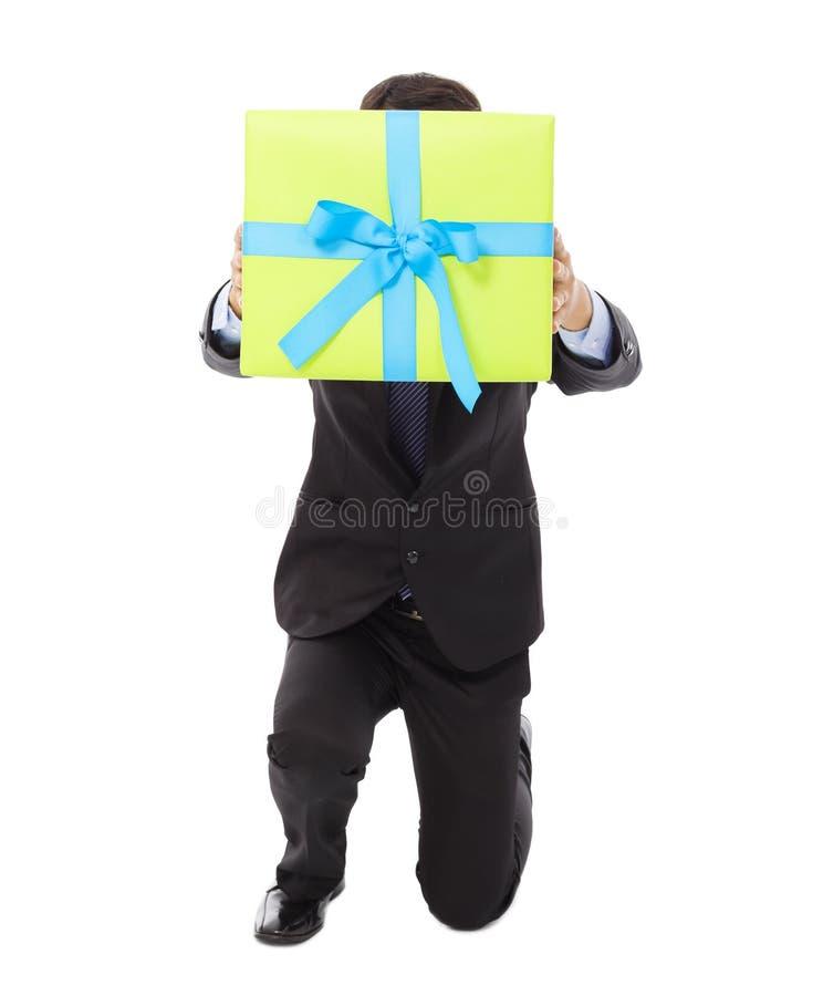 拿着礼物盒的商人和跪下来 免版税库存照片
