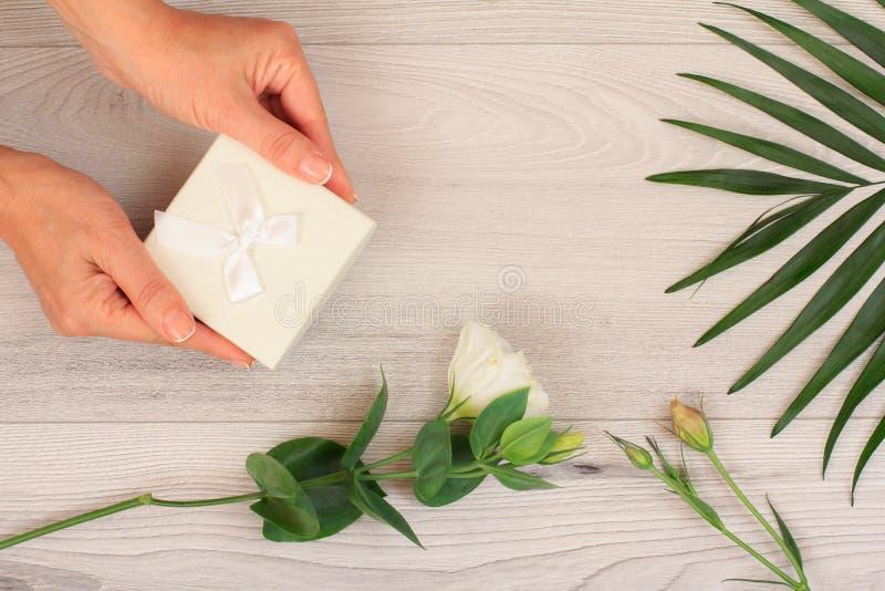 拿着礼物盒的妇女被栓在有花的手上在背景 库存照片