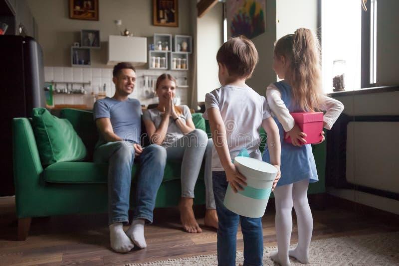 拿着礼物盒的孩子做意外对于父母,背面图 库存图片