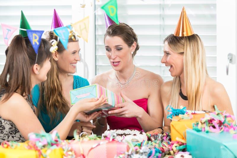 拿着礼物盒的快乐的妇女在惊奇生日聚会期间 免版税库存图片
