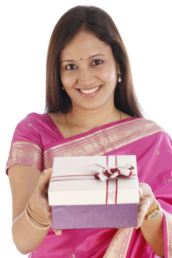 拿着礼物盒的愉快的年轻印地安传统妇女 库存图片