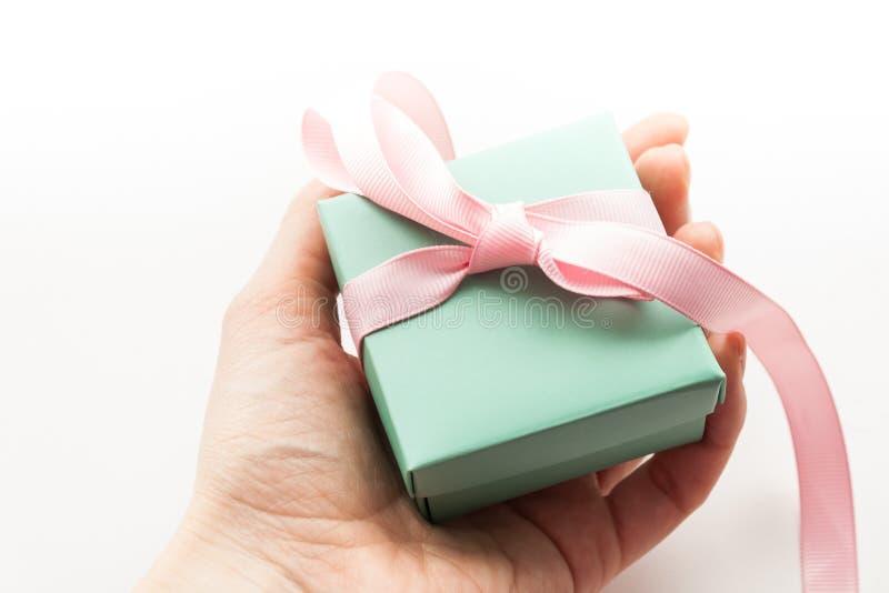 拿着礼物盒的手被隔绝在白色背景 免版税库存图片
