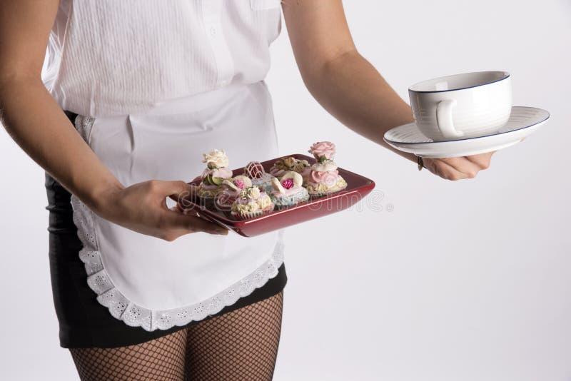 拿着神仙蛋糕的女服务员的手和茶杯 库存图片