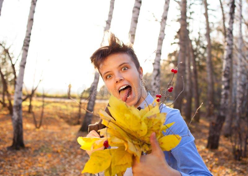 拿着秋叶的花束人 图库摄影