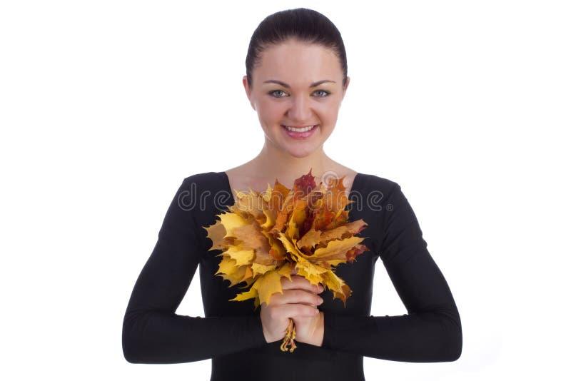 拿着秋天橙色槭树的女孩在白色离开 库存图片