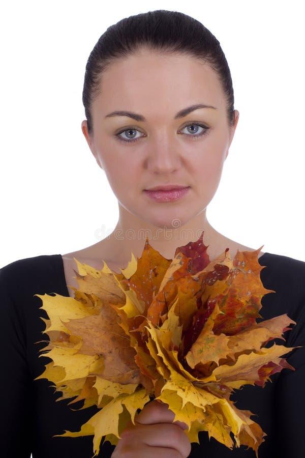 拿着秋天橙色槭树的女孩在白色离开 库存照片