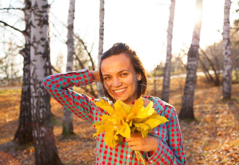 拿着秋天的花束青少年的女孩妇女 免版税库存照片