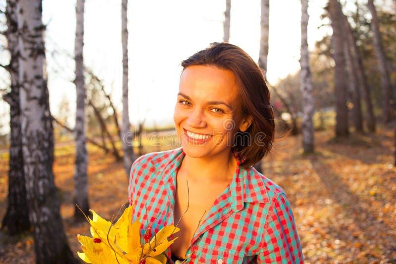 拿着秋天的花束青少年的女孩妇女 库存图片
