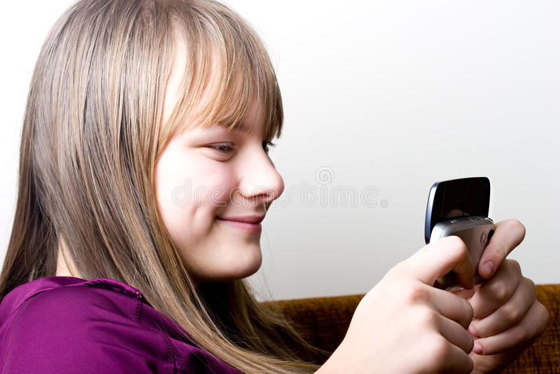 拿着移动电话少年texting的年轻人的女孩 免版税库存照片