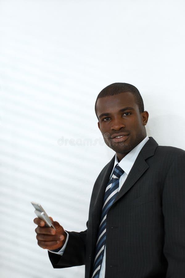 拿着移动电话的生意人 免版税库存照片