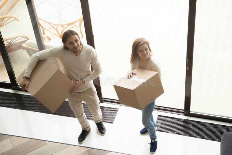 拿着移动的箱子的年轻夫妇进入新房,顶上的v 库存图片