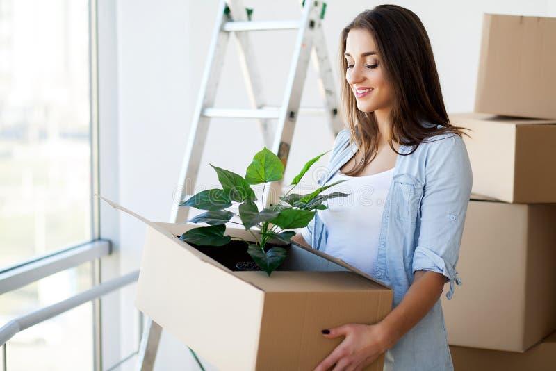 拿着移动的箱子的愉快的年轻妇女在A的空的屋子里 免版税库存照片