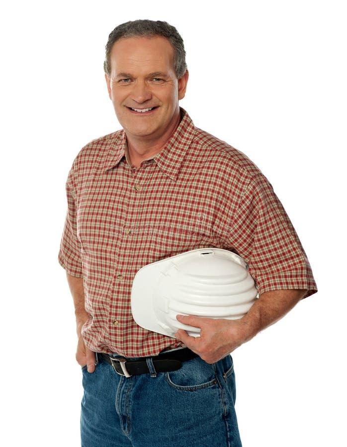 拿着空白安全性帽子的微笑的高级建筑师 免版税库存照片