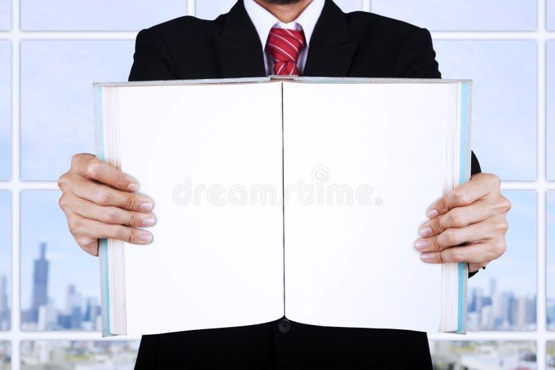 拿着空白开放书的商人在办公室 免版税库存照片