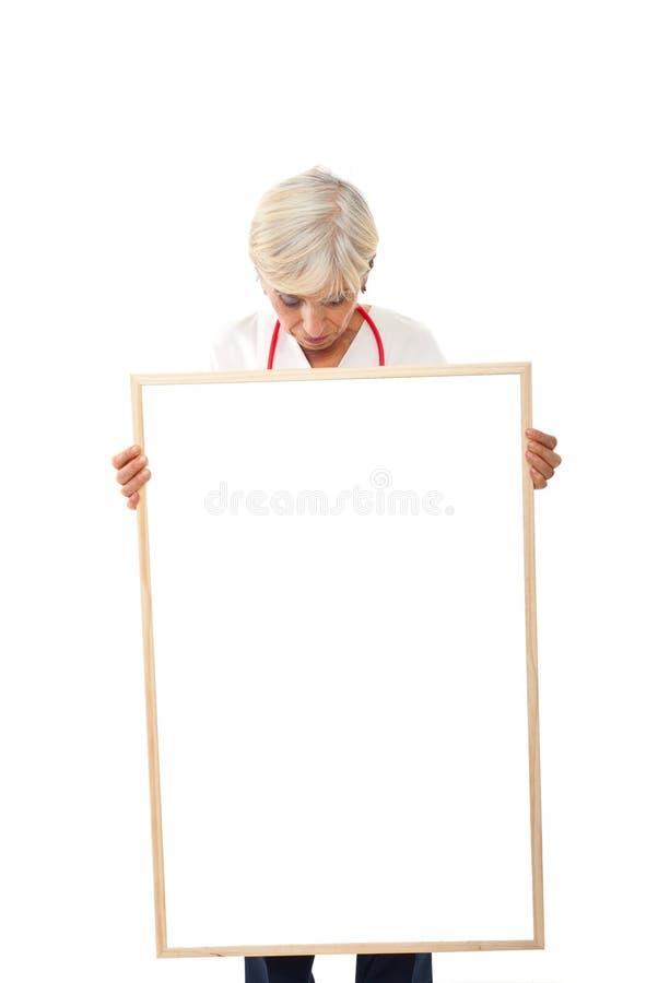 拿着空白海报的高级妇女 图库摄影