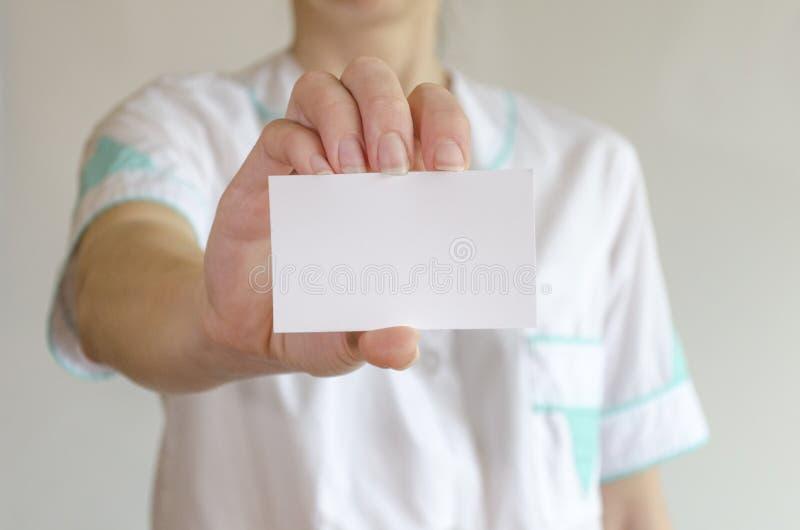 拿着空白的名片的医生的手 免版税图库摄影