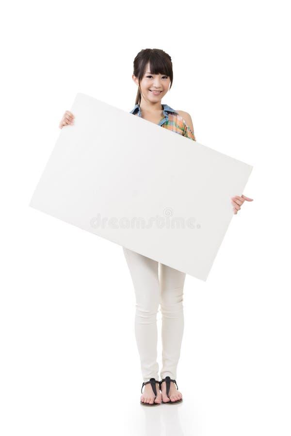 拿着空白的委员会的可爱的年轻亚裔妇女 免版税库存照片